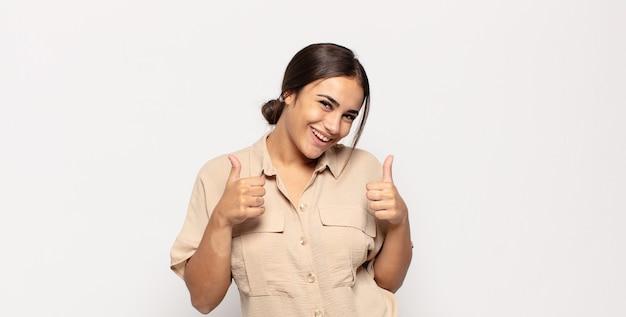 두 엄지 손가락으로 광범위하게 행복하고 긍정적이며 자신감 있고 성공적인 찾고 웃는 예쁜 젊은 여자