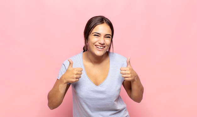Pretty young woman smiling broadly looking happy, positive, confident and successful, with both thumbs up