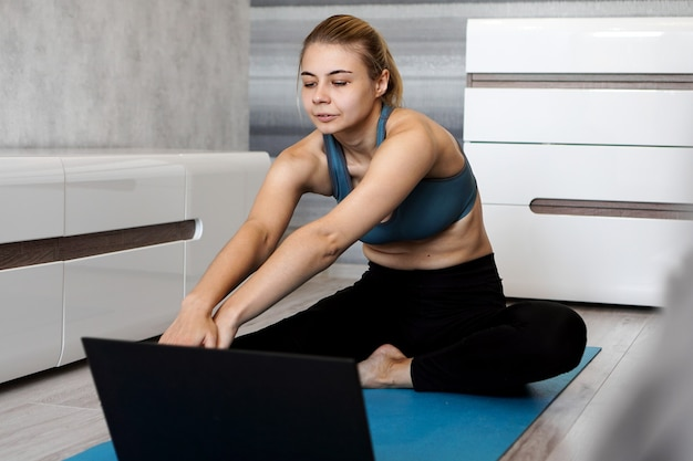 Pretty young woman in sportswear watching online video on laptop