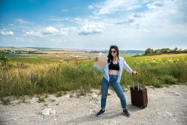 예쁜 젊은 여자가 서서 도로지도를보고 자연에서 여름 휴가를 즐기십시오.