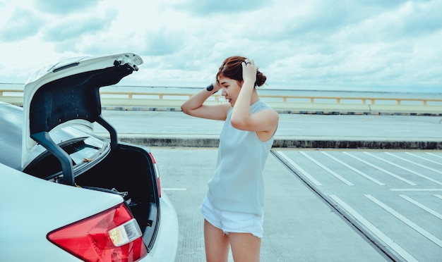 꽤 젊은 여자가 서서 손 도구를 야외에서 차 뒤를 보고 있습니다.