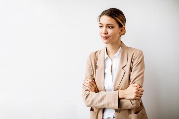 현대 사무실에서 흰 벽에 서있는 예쁜 젊은 여자