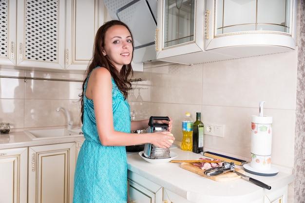 生の刻んだ肉のプレートが並んで立っている彼女のレシピのために彼女の台所の粉チーズで料理をしているかなり若い女性