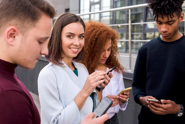 Pretty young woman standing between her friends using mobile phones looking at camera