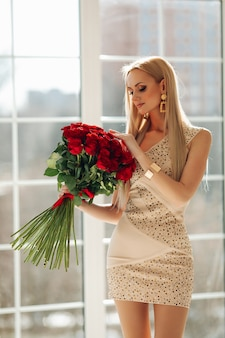 Pretty young woman standing and holding bouquet of red roses