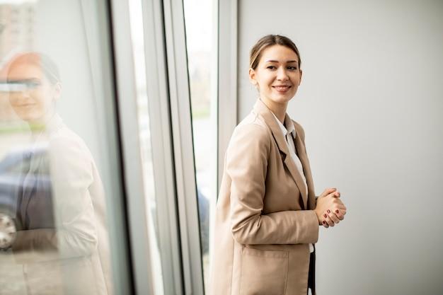 Довольно молодая женщина, стоящая в современном офисе