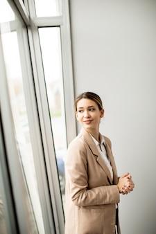 현대 사무실에 서있는 예쁜 젊은 여자