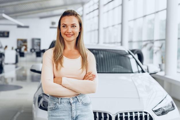 車のショールームで新車の近くに立っているかなり若い女性
