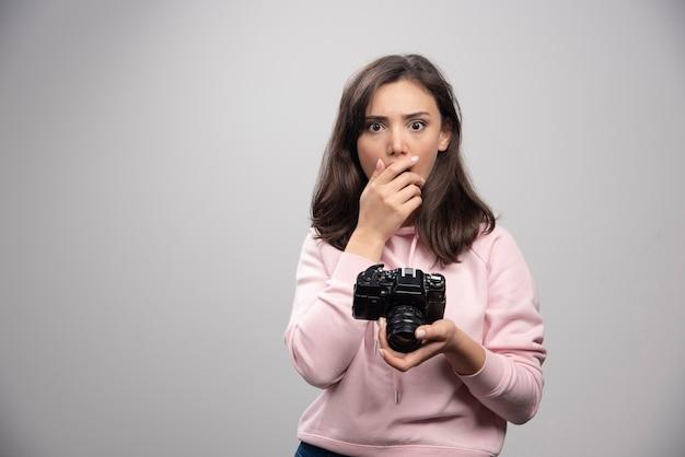 灰色の壁の上にカメラで立っているかなり若い女性。