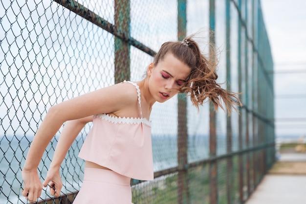 金網フェンスの近くで目を閉じて立っているかなり若い女性