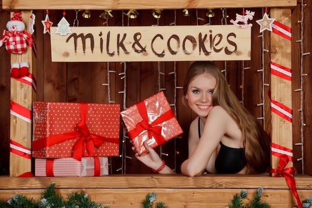 かわいらしい若い女性が、贈り物と「ミルクとクッキー」と書かれた窓に立ち、飾られた部屋でクリスマスセットを開催します。