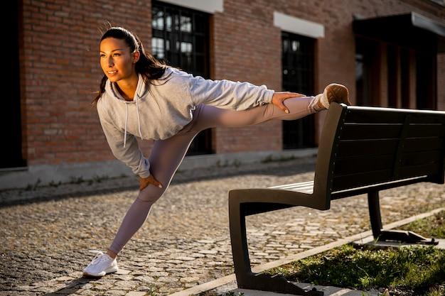 도시 환경에서 훈련하는 동안 스트레칭 예쁜 젊은 여자