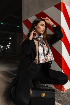 Pretty young woman in stylish black coat with silk elegant scarf in boots with leather bag sits on the asphalt in parking lot near pillar in a red-white lines. urban girl fashion model rests outdoors.