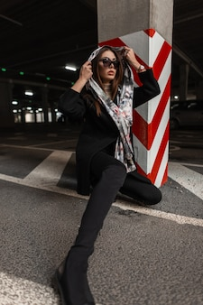 Pretty young woman in stylish clothes puts vintage silk scarf on head outdoors. fashionable girl in dark sunglasses in trendy black outerwear poses near red-white striped column on the city. elegance.