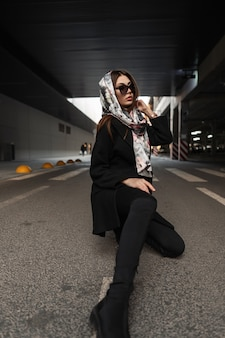 Pretty young woman in stylish clothes in vintage silk scarf on head in dark fashionable sunglasses in trendy black outerwear poses outdoors. fashionable girl relaxes on road on the city. elegance.