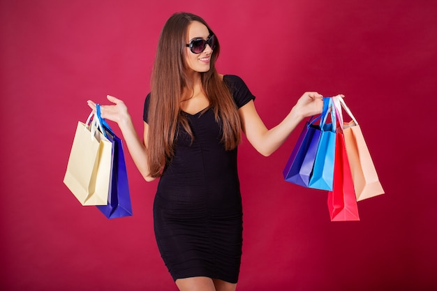 Pretty young woman stylishly dressed in black with bags after shopping