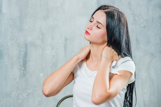 Pretty young woman suffering from neck pain sitting against gray wall