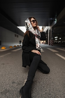 Pretty young woman in sunglasses in stylish black coat with silk elegant scarf on head in boots in jeans sits on the asphalt in parking in the street. urban american girl fashion model rests outdoors.