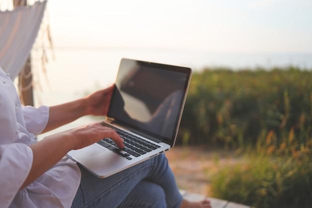 Довольно молодая женщина, серфинг в интернете на ноутбуке на открытом воздухе