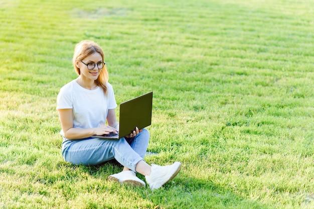 屋外のラップトップでインターネットサーフィンをしているかなり若い女性。