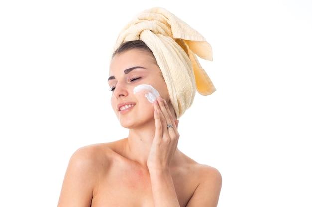 예쁜 젊은 여자는 흰 벽에 고립 된 크림으로 얼룩진 머리에 수건으로 그녀의 피부를 돌 봅니다.