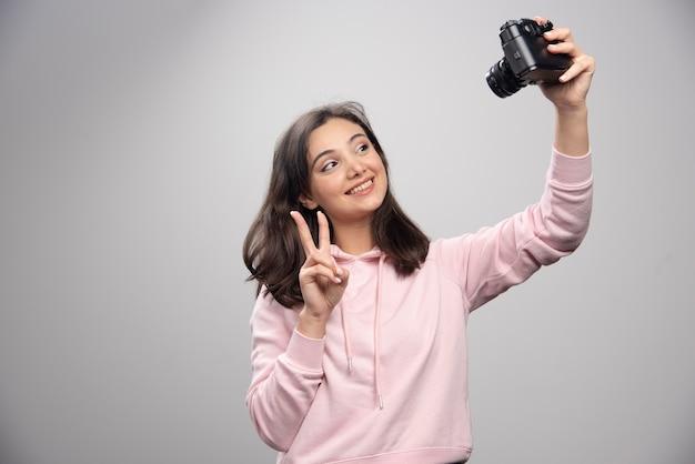 회색 벽에 카메라와 함께 selfie를 복용 꽤 젊은 여자.