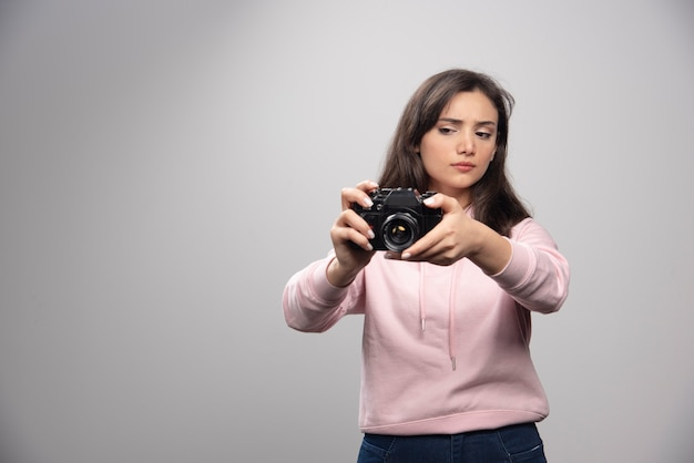 Pretty young woman taking pictures with camera over a gray wall.