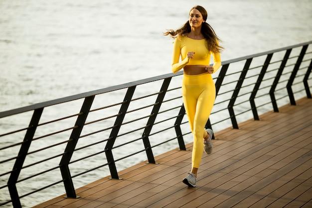 Довольно молодая женщина делает упражнения на набережной реки