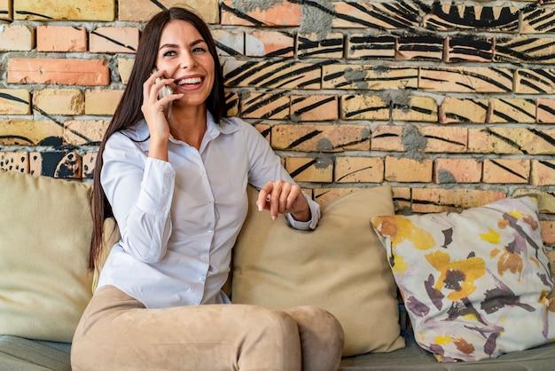 Довольно молодая женщина разговаривает по мобильному телефону в кафе