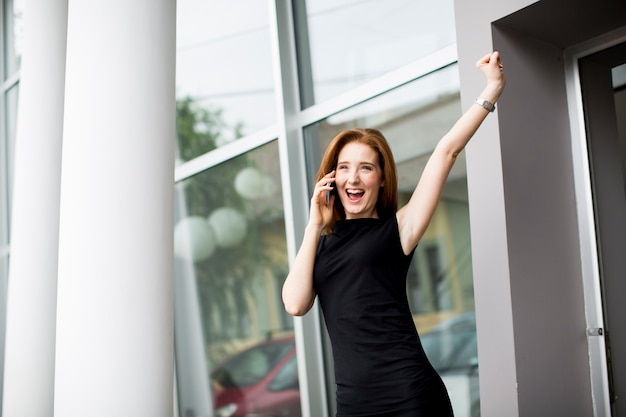Pretty young woman talking on the phone in front of office