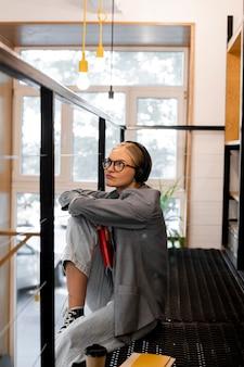 Donna abbastanza giovane che pensa alla biblioteca