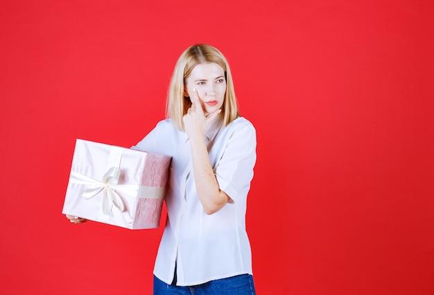 かなり若い女性が彼女の顔に手を置いている間に彼女に送られた贈り物について考えます