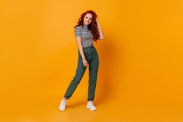 Pretty young woman touches her curly red hair and smiles. portrait of girl in jeans and top in orange studio.