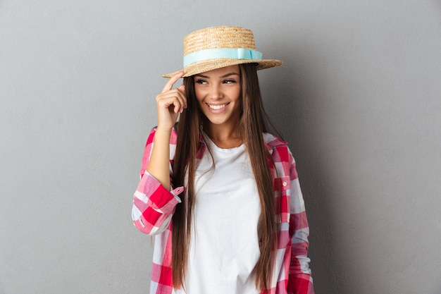Pretty young woman, touching her straw hat, looking away