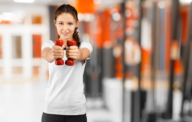 かなり若い女性がジムでトレーニング