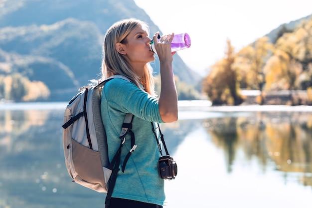 湖の前に立っている間バックパック飲料水を持つかなり若い女性旅行者。