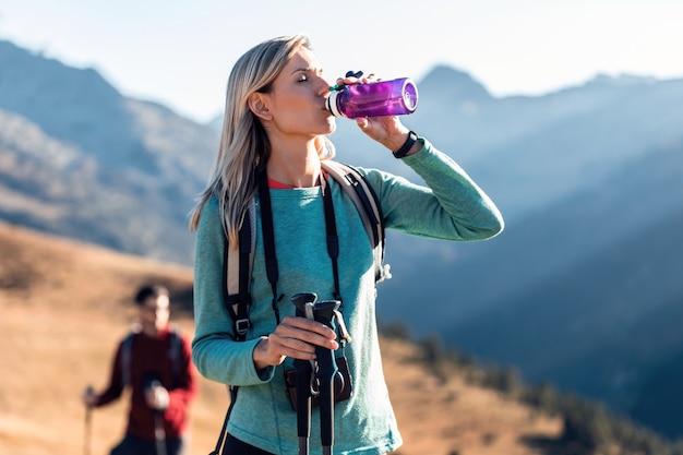 山に立っている間バックパックの飲料水を持つかなり若い女性旅行者。