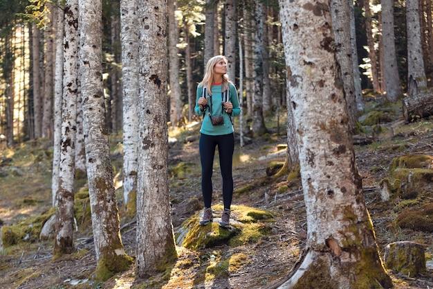 Довольно молодая женщина-путешественник с рюкзаком, глядя в сторону в естественном лесу.