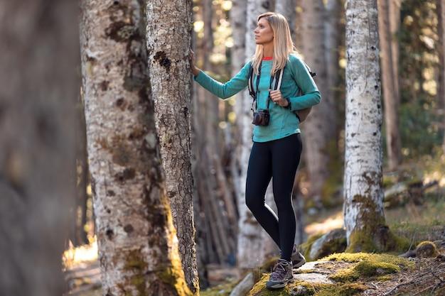 Довольно молодая женщина-путешественник с рюкзаком, глядя в сторону, опираясь на дерево в естественном лесу.