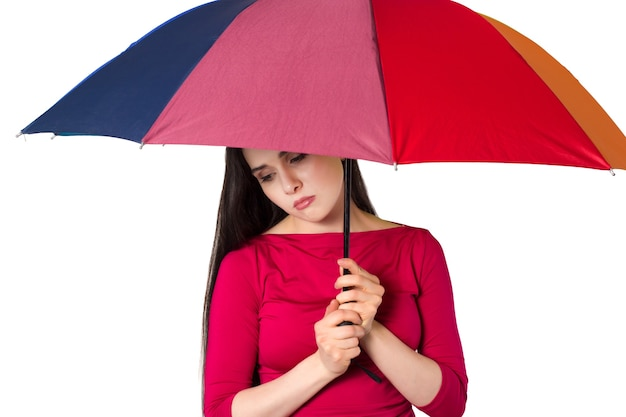 カラフルな傘の下で、白い背景で隔離のかなり若い女性