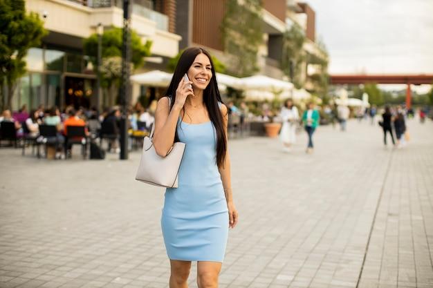 通りを歩きながら携帯電話を使用してかなり若い女性