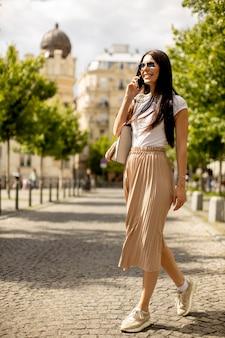 Довольно молодая женщина с помощью мобильного телефона во время прогулки по улице