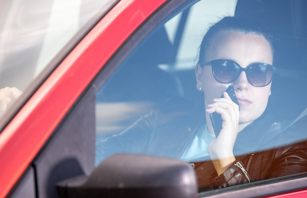 スマートフォンを使用してかなり若い女性、車を運転しながら携帯電話、交通機関の概念