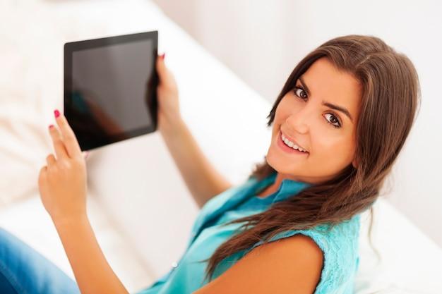 Bella giovane donna utilizzando la tavoletta digitale a casa