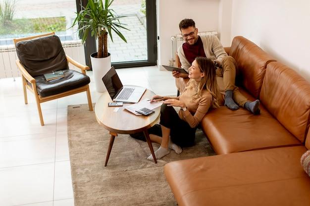 Довольно молодая женщина с помощью ноутбука и молодой человек с помощью цифрового планшета, сидя на диване у себя дома