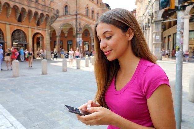 Довольно молодая женщина с помощью смарт-телефона на улице старого города. концепция технологии и коммуникации.