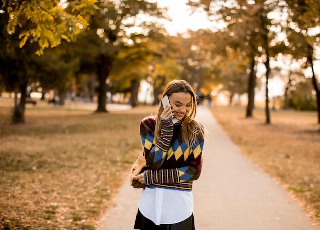 Довольно молодая женщина гуляет в осеннем парке и пользуется мобильным телефоном
