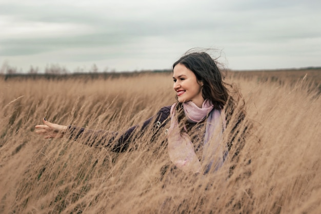 Pretty young woman walking on a wheat field.
