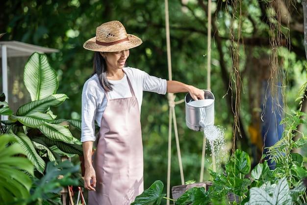 여름 화창한 날에 정원에서 나무를 급수하는 예쁜 젊은 여자. 여자 여름 자연에서 외부 원예입니다. 농업, 원예, 농업 및 사람들 개념.