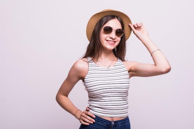 Милая молодая женщина нося шляпу, солнечные очки изолированные над белой предпосылкой
